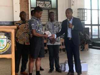 Dr. Godson Afful presents copies of his book 'Charisma Plus Character' to Adisadel College
